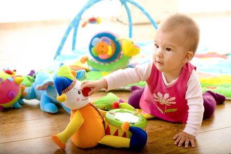 Foto de Baby girl (9 months) playing with soft toys at home. Toys are property released.  - Imagen libre de derechos