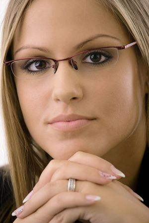 Closeup portrait of young businesswomen wearing glasses. Thinking, leaning on hands, looking at camera. Isolated on white background.