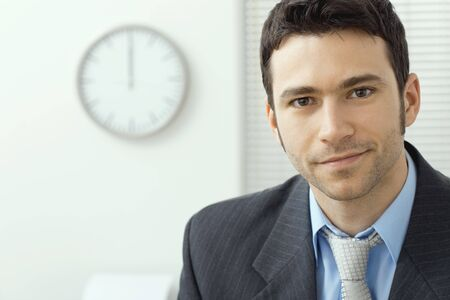 Portrait of young handsome businessman at office, smiling.
