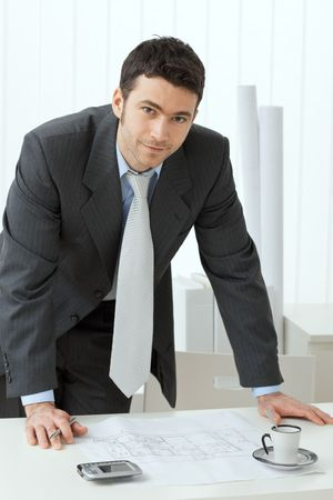 Photo pour Architect wearing grey suit leaning on office desk with floor plan on it. Looking at camera, smiling. - image libre de droit