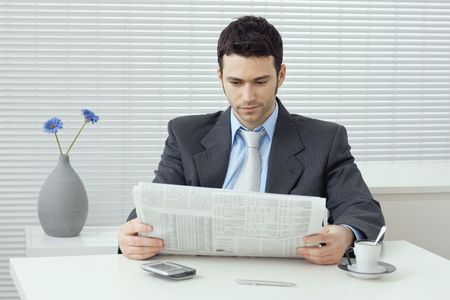 Young businessman having coffee break, sitting at office desk and reading newspaper.