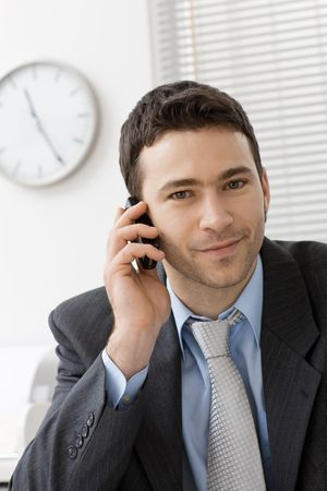 Happy businessman talking on mobile phone in office, smiling.