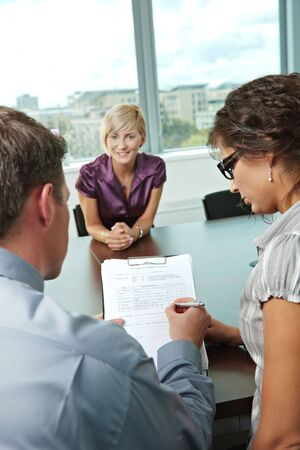 Conductors holding questionnaire form during the job interview, applicant\'s reults are excellent. Focus placed on sheet in front.