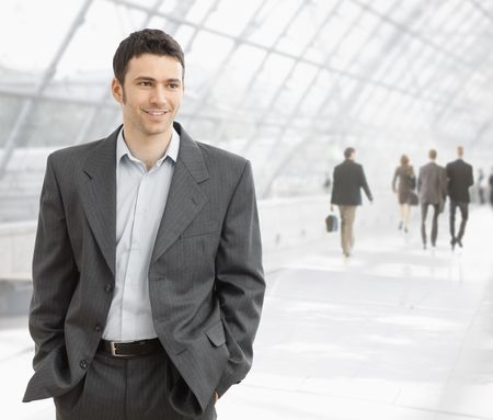Young businessman standing in office hallway with hands in his pocket, smiling.