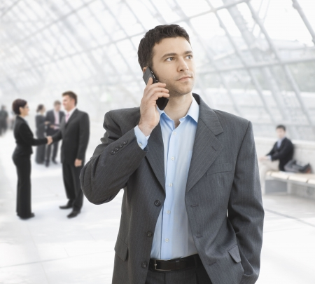Young businessman talking on mobile standing in office hallway.
