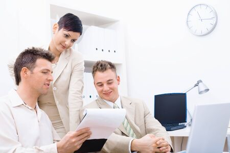 Three young businesspeople having business meeting, looking at document and smiling.