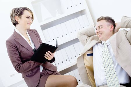 Satisfied businessman sitting at desk in office, smiling and looking up to his secretary, holding personal organizer.