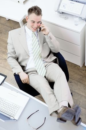 Satisfied businessman sitting by desk at office, feet on table, talking on mobile phone, smiling. High-angle view.