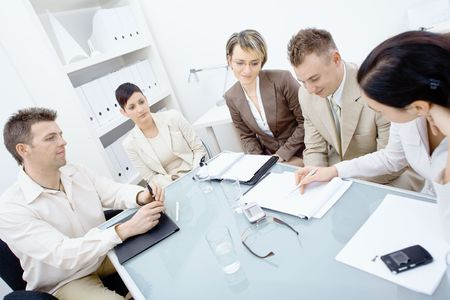 Five businesspeople sitting around table in office and having a meeting. Writing and discussing notes on paper.の写真素材