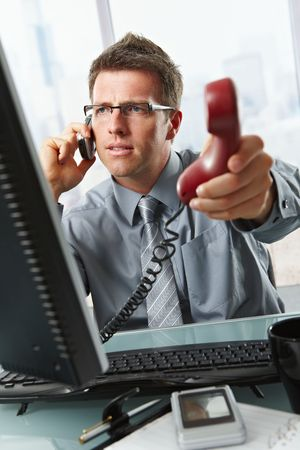 Businessman with glasses busy talking on mobile phone handing over landline call to answer in office.