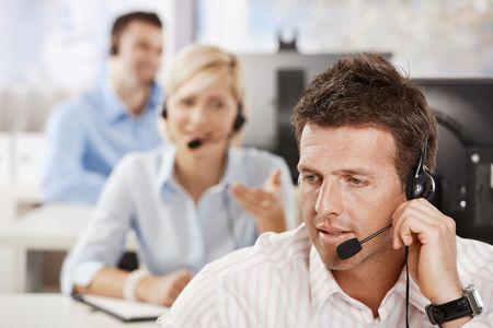 Portrait of customer service operator talking on headset, smiling.