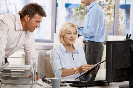 Businesspeople working together in office, looking at notepad, smiling.