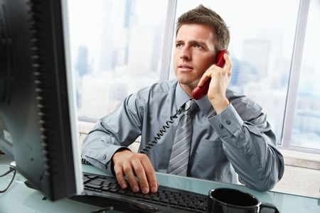 Determined businessman discussing computer work on landline phone while looking at screen typing on keyboard at office desk.
