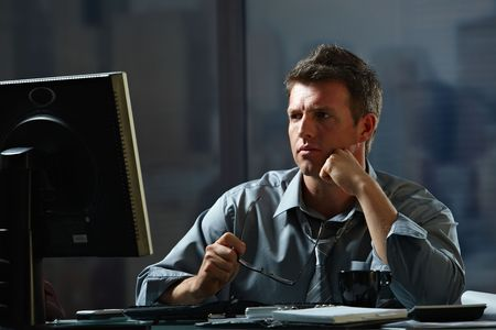 Tired businessman working late on computer in office holding glasses in hand.