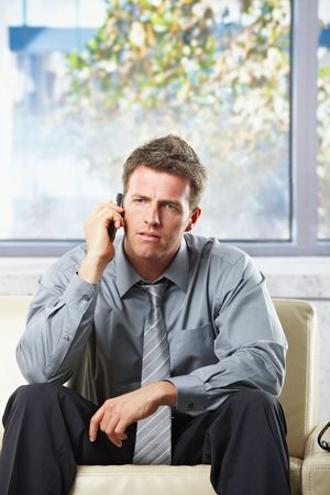 Troubled businessman focusing on phonecall sitting on leather couch thinking.