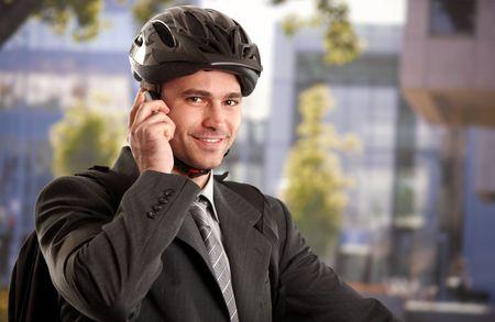 Portrait of young businessman wearing bike helmet, talking on mobile phone, outdoors.