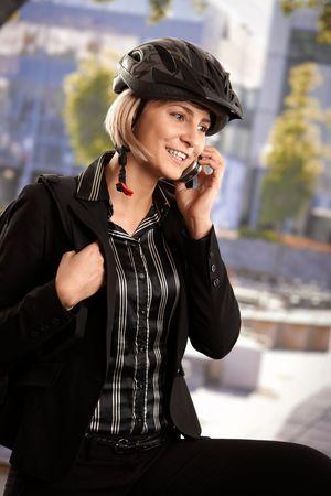 Portrait of young businesswoman wearing bike helmet, talking on mobile, outdoors.