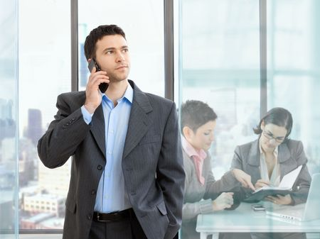 Businesswoman talking on mobile phone in modern office. Businesswomen working at desk in the background.