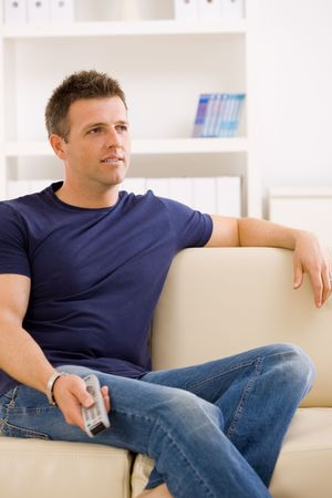 Man watching TV at home, sitting on beige couch, holding remote control in hand.
