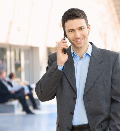Portrait of happy businessman talking on mobile in office hallway.