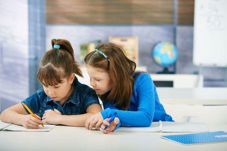 Children sitting at desk working together in primary school classroom.  Elementary age children.