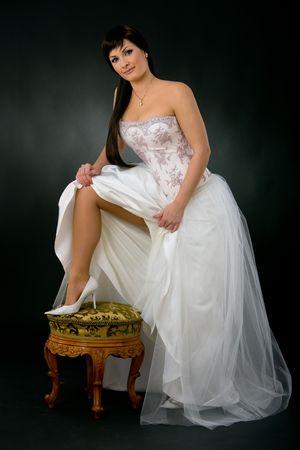 Photo pour Beautiful bride showing her leg in white shoe. - image libre de droit