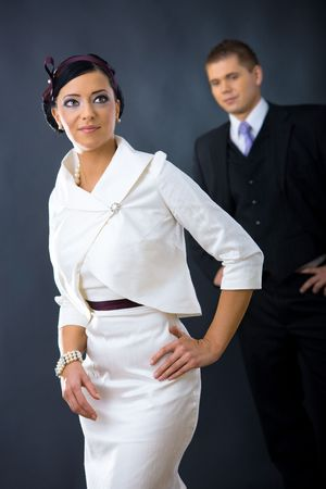 Portrait of young woman wearing white cocktail shirt with jacket, standing with hands on hip. Man in the background wearing three-pieces dark suit.