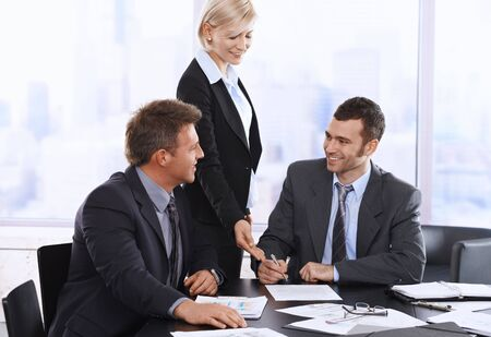Photo pour Businessman signing contract at meeting, smiling assistant pointing at document. - image libre de droit