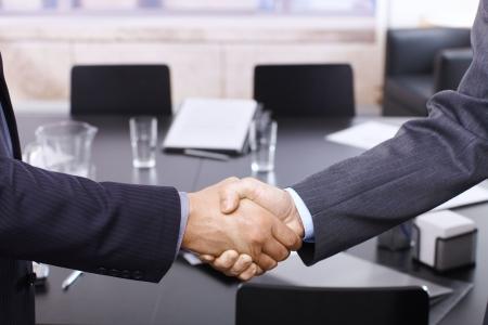 Handshake in closeup, business meeting in office.