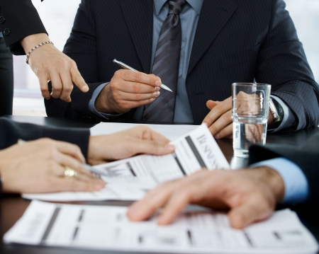Hands in closeup at businessmeeting focusing on business documents and pointing at papers to sign.