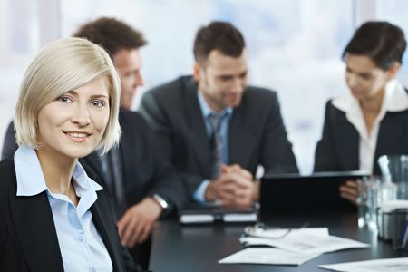 Photo pour Portrait of mid-adult businesswoman smiling at camera with colleagues at meeting in background, - image libre de droit