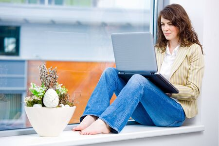 Young happy businesswoman sitting in office window and wokring on laptop computer, smiling.