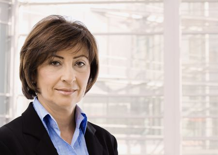 Closeup portrait of senior businesswoman in black suit and blue shirt, smiling and looking at camera, in front of windows.
