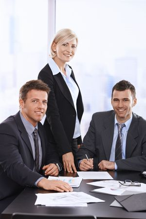 Portrait of smiling businesspeople at meeting table in office.