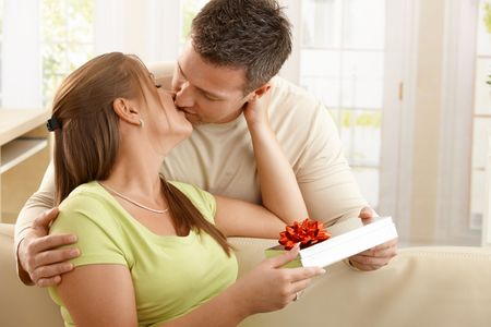 Kissing couple sitting on sofa, man handing present over to woman.