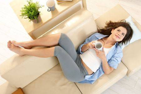 Photo pour In high angle view girl lying on living room couch with feet up, smiling, holding mug in two hands. - image libre de droit