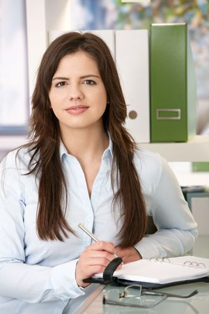 Photo pour Portrait of young woman looking confidently at camera in office. - image libre de droit