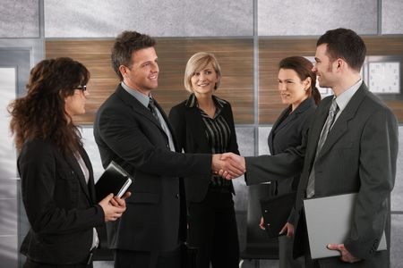 Happy businesspeople shaking hands greeting each other before business meeting in office.