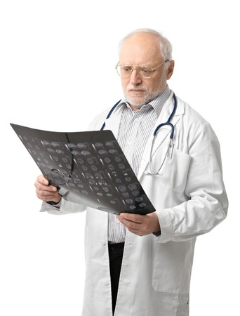 Portrait of serious senior doctor looking at X-ray image. Isolated on white background.