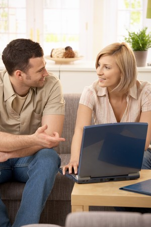 Smiling couple sitting at home in discussion, using laptop.