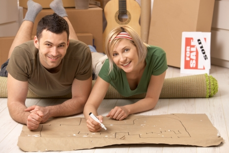 Portrait of smiling couple lying on floor of new house making plan to furniture their home together on paper.の写真素材