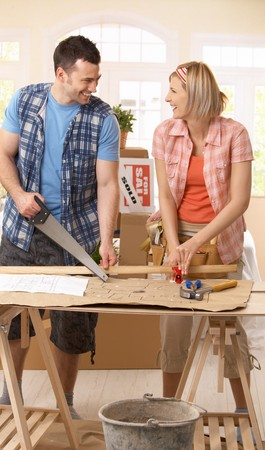 Photo pour Happy couple improving new house, working together at table. - image libre de droit