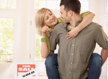 Young man taking smiling girlfriend on back into new house, woman holding keys.