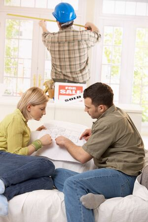 Young couple sitting in new house, looking at ground plan, builder measuring window size in background.