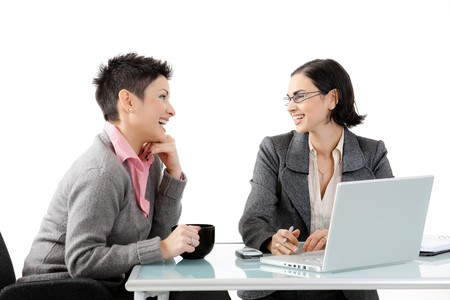 Young businesswomen sitting at office desk, looking at each other, smiling. Isolated on white.