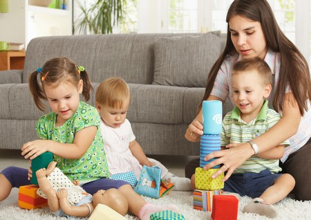 Mother and 3 happy children sitting on floor at home playing together with toy blocks smiling.