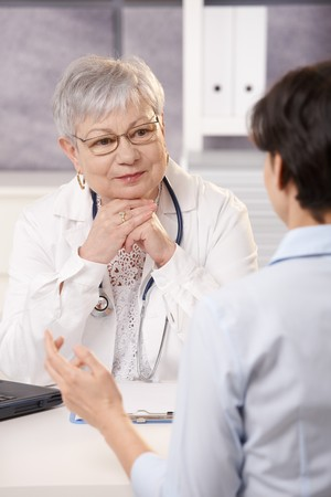 Senior doctor listening to patient in office, smiling.