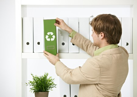 Man drawing out green folder with recycling symbol in office.