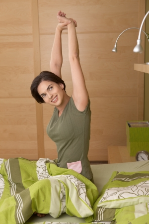Smiling woman waking up, stretching, sitting in bed in morning.