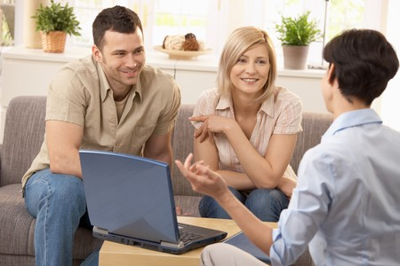 Advisor and smiling couple in discussion in bright living room.